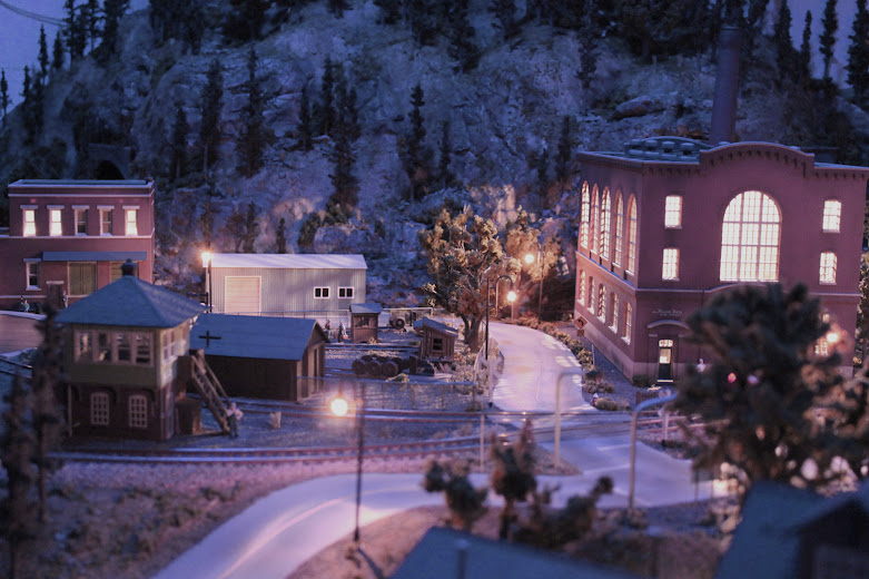 HO scale model railroad layout industrial scene at night with accessory lighting effects