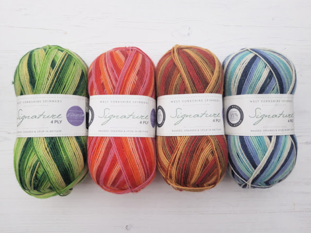 Four balls of yarn lined up on a white board background.  The balls are from left to right: shades of green, shades of pink, shades of brown and yellow, shades of blue and turquoise