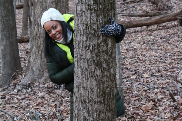 Woman peeking from behind a tree