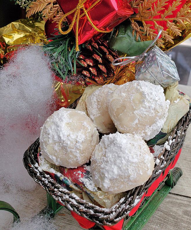 these are snowball cookies also called Mexican wedding cakes in a sleigh with fake snow and Christmas decorations in the background