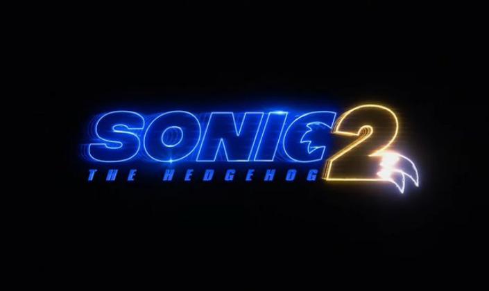Imagem: fundo preto com o título em azul néon que diz Sonic e um número 2 em amarelo com o formato de uma cauda de raposa, como a de Tails, dos jogos.