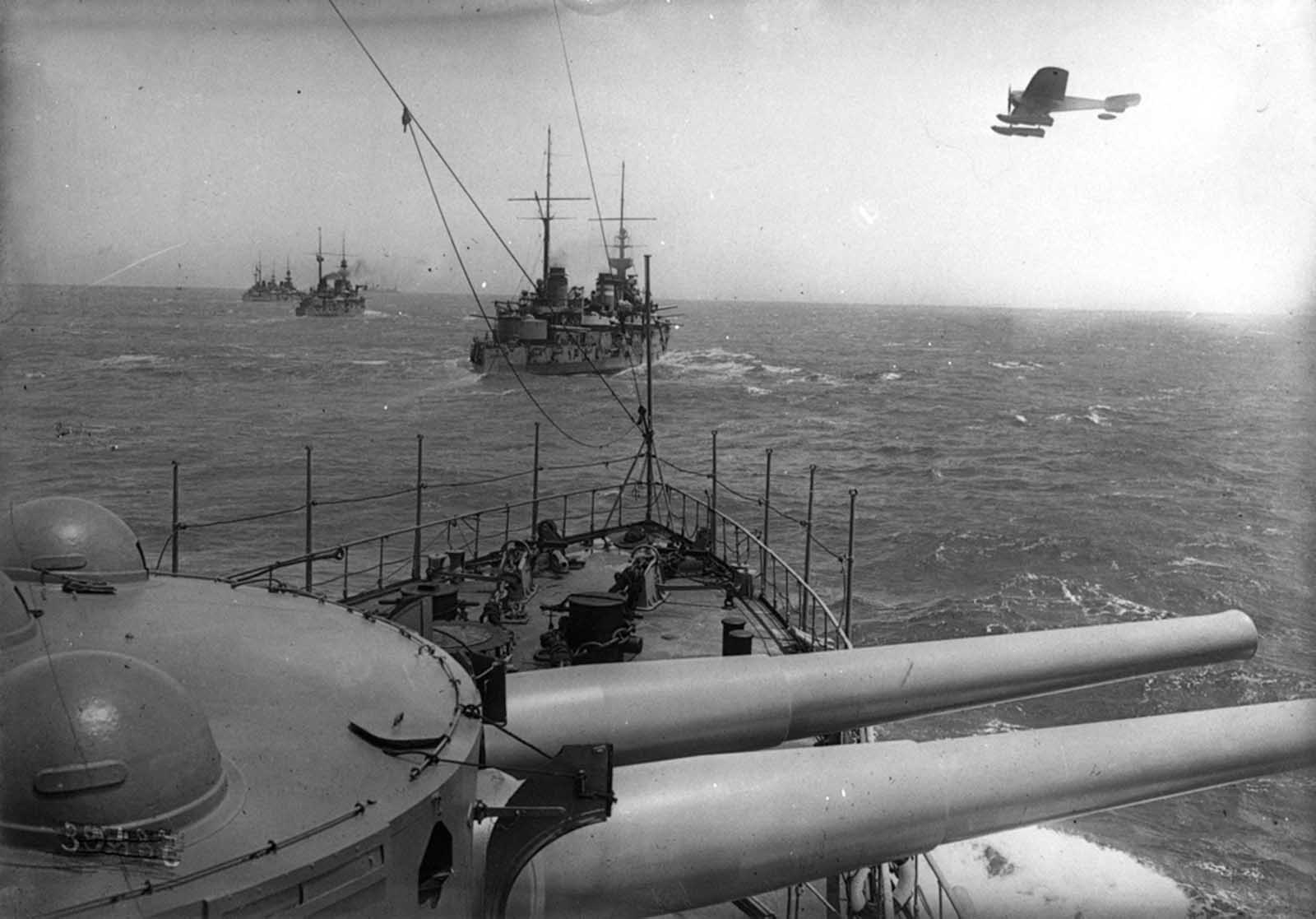 Allied warships at sea, a seaplane flyby, 1915.