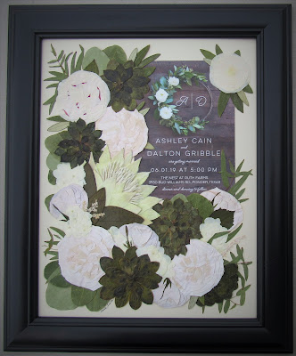Wedding invitation surrounded by pressed bridal flowers
