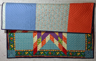 Folded quilt shows part of the front and the background sewn of orange, medium blue, and pale blue print fabrics,