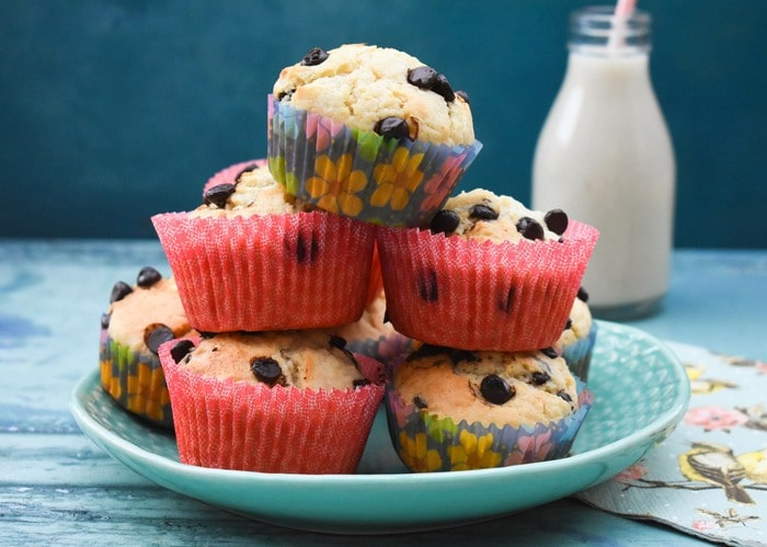 A stack of vegan choc chip muffins in pink and lilac cases on a aqua blue plate