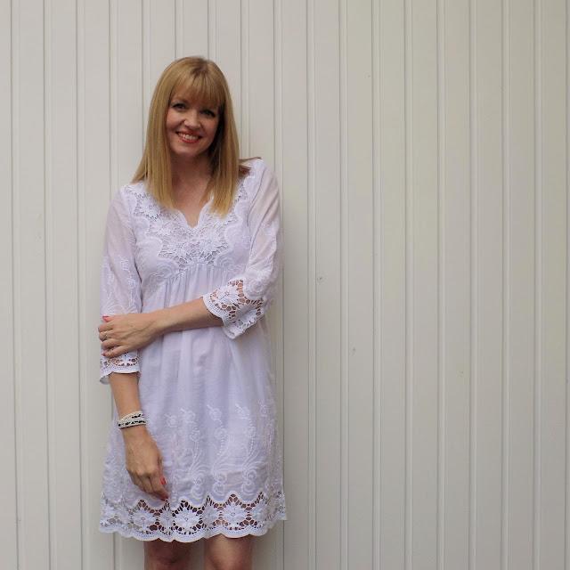 White lace dress, zebra print clutch bag, leopard print wrap bracelet and wedge sandals