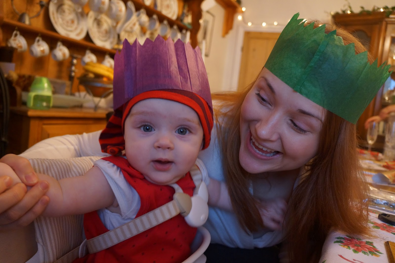 mum and baby wearing traditional british paper crown at christmas dinner