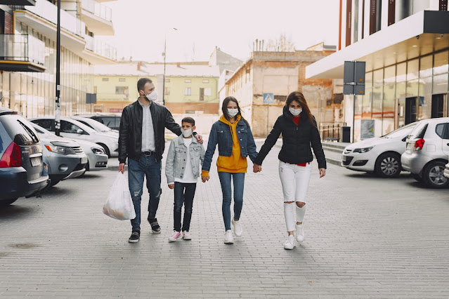 A family wearing face masks and walking back to the ride after shopping.