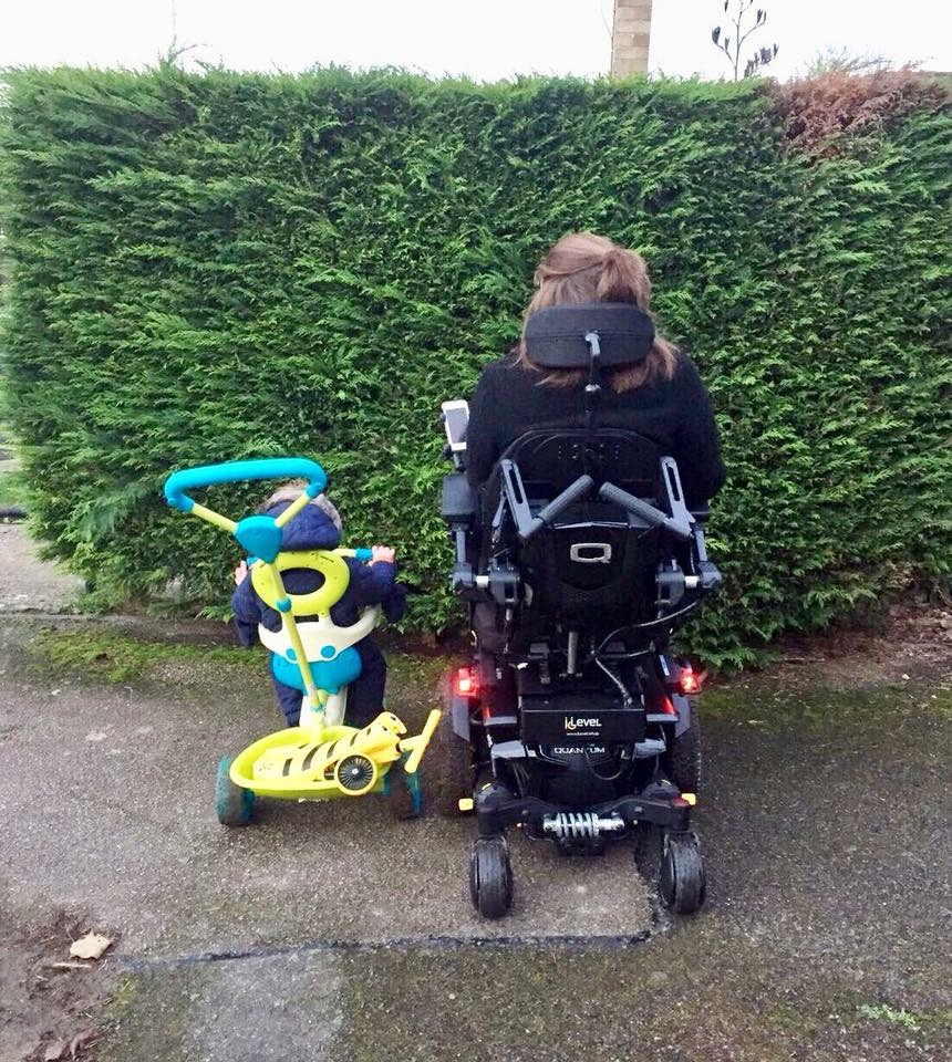 Image is taken from behind, Shona is sitting in her powerchair next to her 1 year old nephew in a green and blue trike.