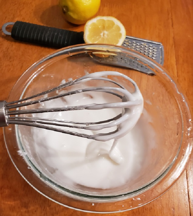This is a bowl of lemon frosting for a lemon loaf cake using a whisk and real lemons grated with a grater