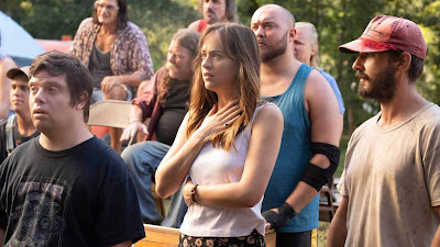 The Peanut Butter Falcon 2019 movie still where Zack Gottsagen, Dakota Johnson, and Shia LaBeouf watch a live wrestling match in someone's backyard