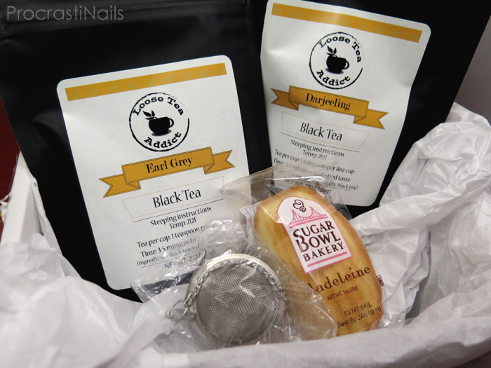 Picture of the contents of my tea subscription box including two full sized teas, a steeping ball and a Madeleine cookie