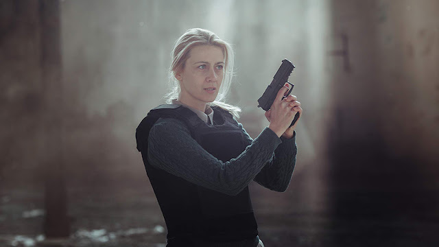 female detective holds a gun