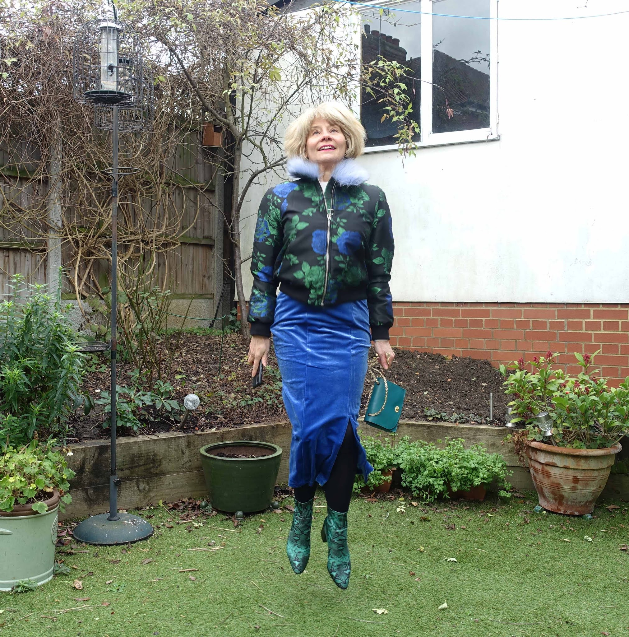 Jumping for joy? Is This Mutton blogger Gail Hanlon in blue and green featuring a velvet midi skirt and snakeskin ankle boots