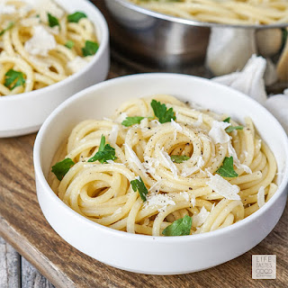 Garlic Butter Sauce for Pasta in a white bowl garnished with Parmesan & parsley