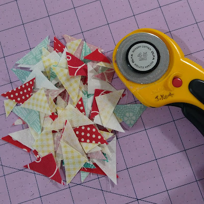 Pile of small fabric triangles beside rotary cutter