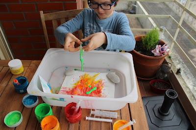 Criança a pintar, rodeada de boiões de tinta e seringas