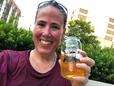 Photo of me post-race. I am sweaty, smiling, and holding a glass of free beer.