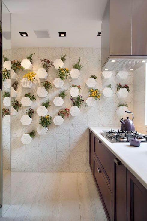 """Para não deixar cômodos espaçosos com aparência de """"vazio"""", é necessário aproveitar todos os cantinhos do ambiente. Dessa forma, você pode brincar com as cores e adicionar itens mais decorativos e menos funcionais na cozinha, como um jardim vertical, por exemplo."""