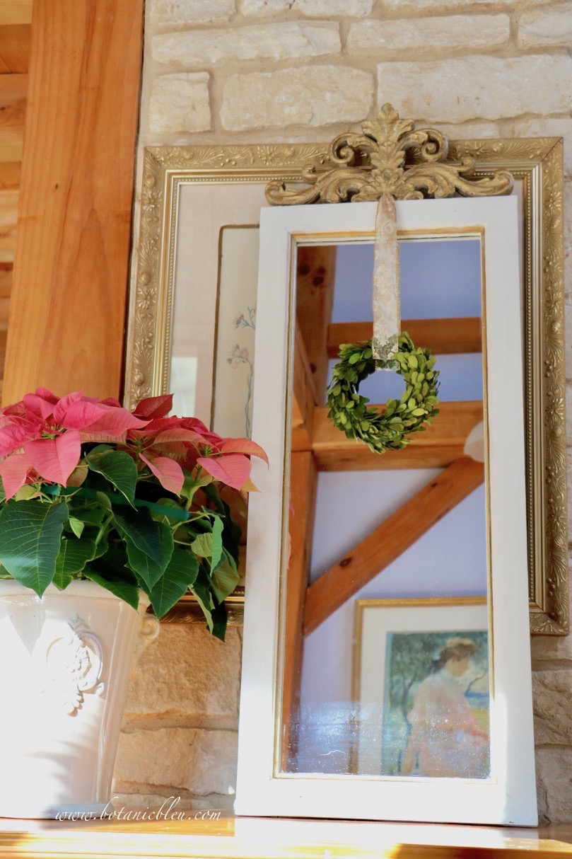 French country mirror decorated for Christmas reflects Impressionist print to multiply French country style in the room