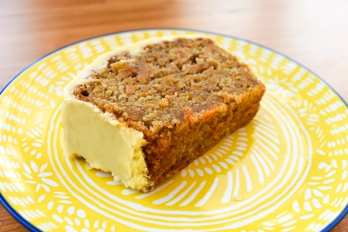 a slice of carrot cake on a yellow side plate