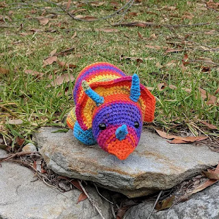A crochet triceratops plushie in a rainbow yarn sitting on a rock in front of a grassy area.