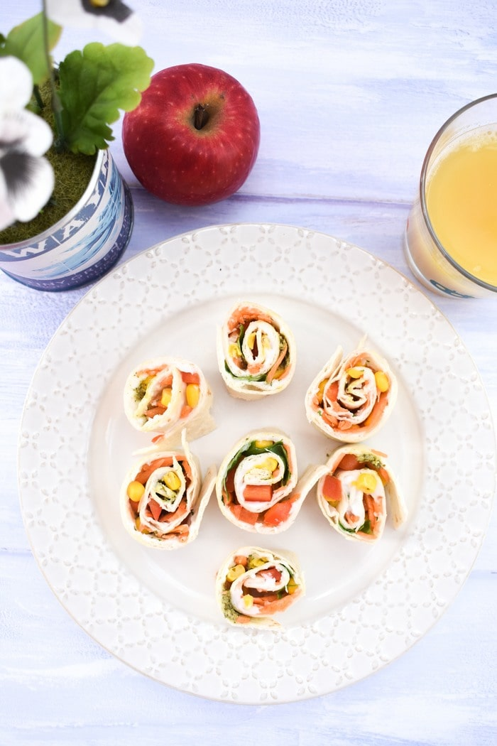 Pinwheel sandwiches on a plate next to a tub of daisies and a glass of orange juice