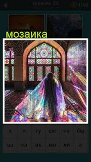 в помещении на окнах сделана мозаика и стоит женщина в солнечных лучах