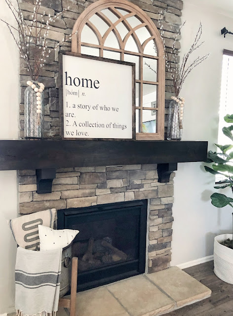 farmhouse styled fireplace, arched mirror, wood sign, glass vases