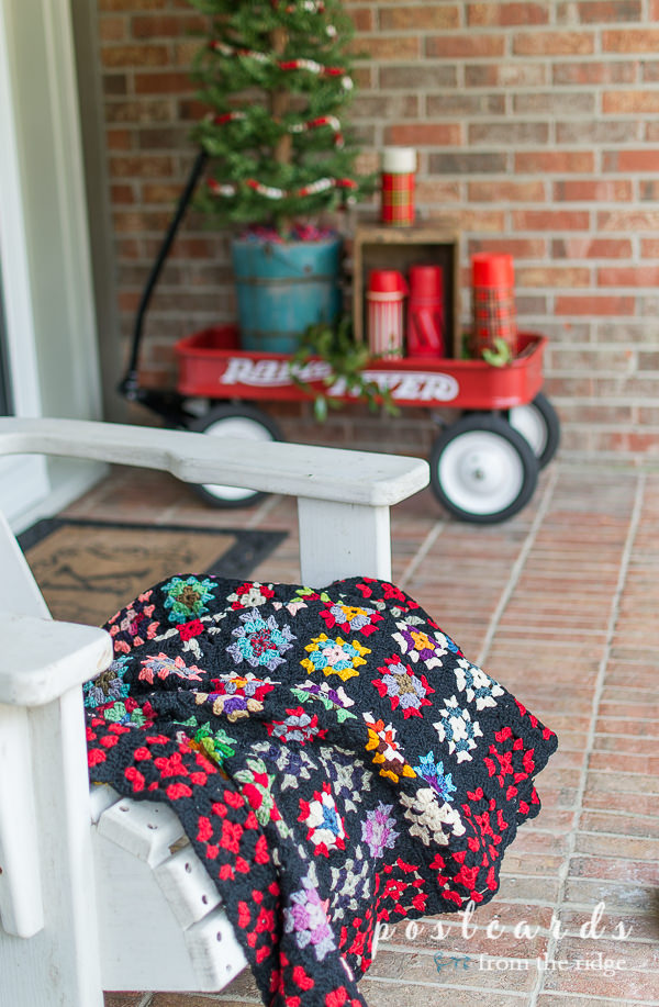 vintage colorful granny square afghan blanket on white porch chair