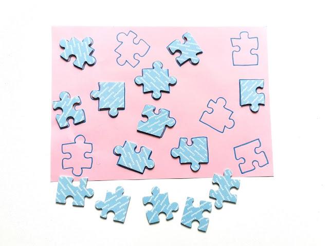 na różowej kartce z kolorowego bloku odrysowane jest czternaście kształtów puzzli, na części z nich leża już dopasowane elementy a reszta leży obok kartki
