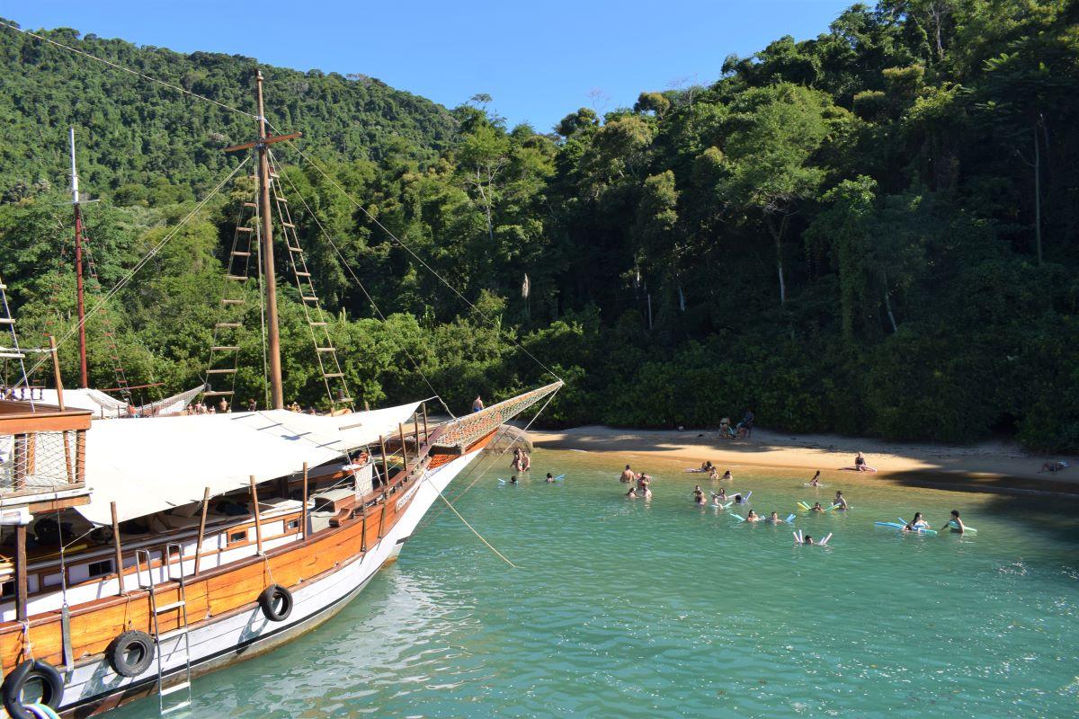 prainha pequena com banhistas nadando e escuna grande ancorada