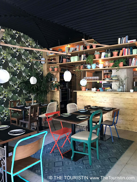Colourful chairs, laid tables, different lampshades, shelves with books over a wooden counter and a palm tree wallpapered feature wall in a restaurant.