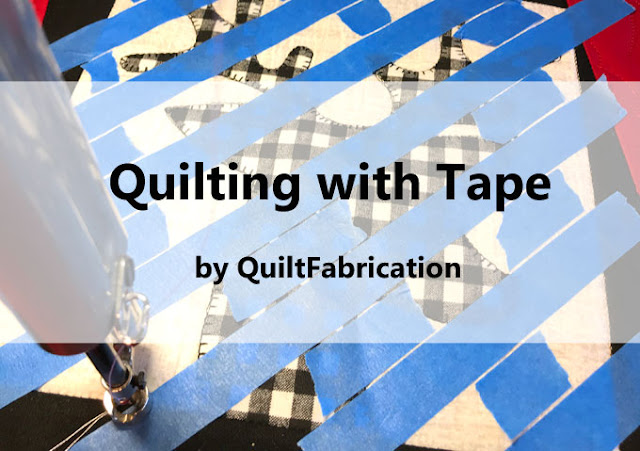 applique quilt block with blue painters tape to mark straight lines for quilting