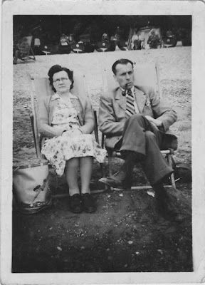A black and white photo of a man and woman sat in deckchaire. The man has a pipe
