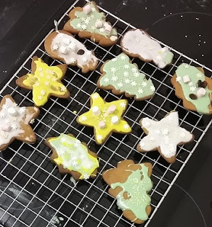 Picture of Christmas biscuits decorated with coloured icing and sprinkles on a cooling rack