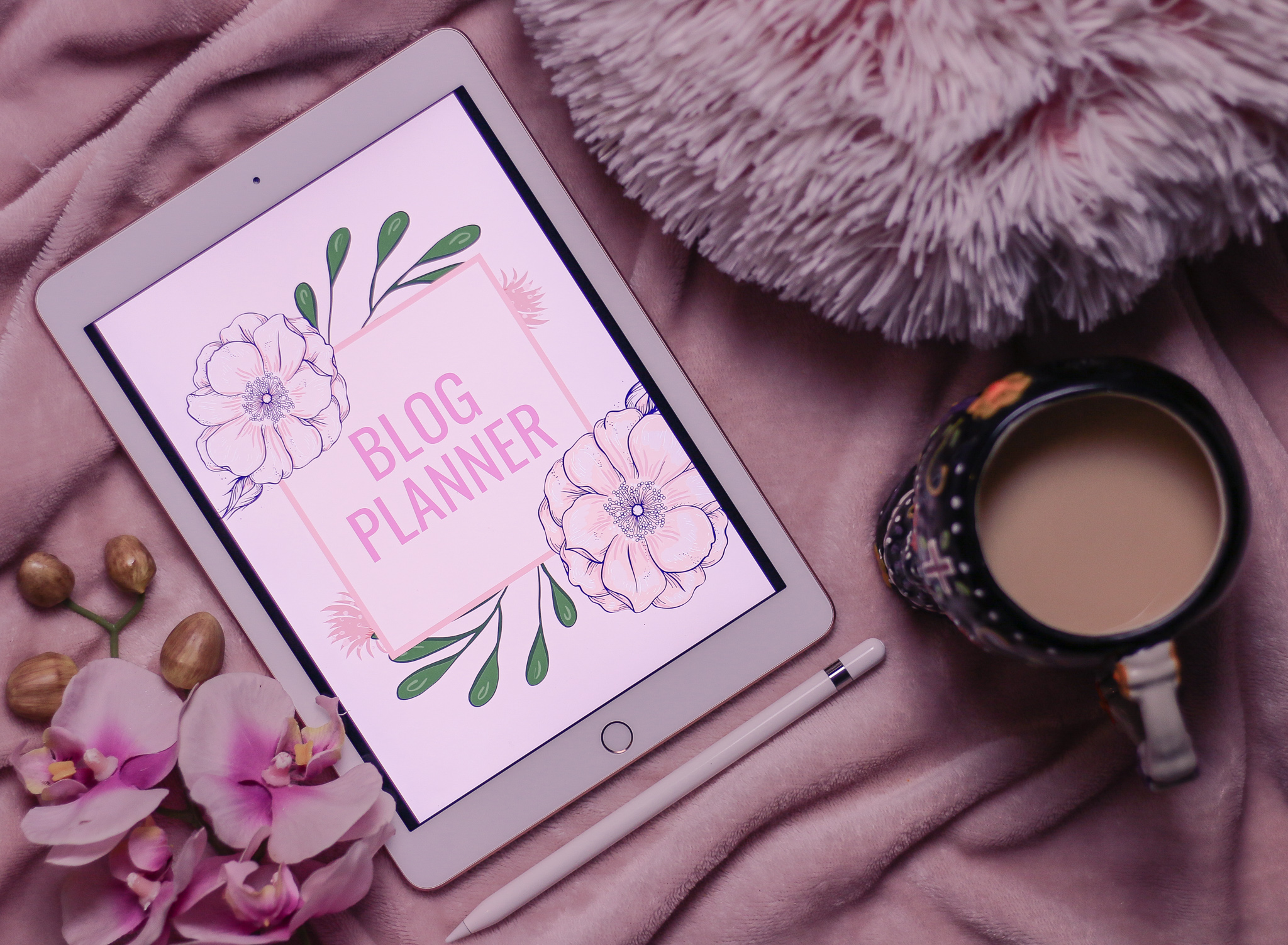 Birds eye view of an iPad on a pink blanket showing the image of a blog planner cover with pink flowers to the left of the photo