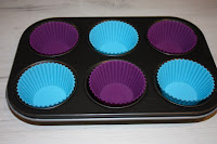 A 6-hole muffin tin with alternate blue and purple silicon muffin cases