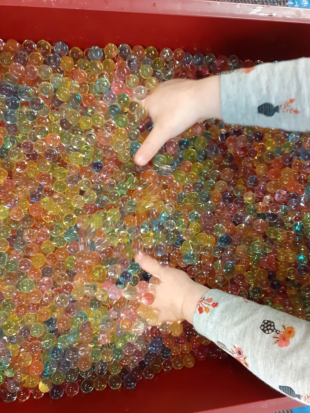 Toddler hands in water beads