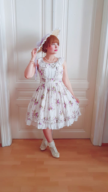 auris wearing a floral dress by magic tea party and a straw bergere hat.
