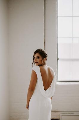 Novia vestida de blanco de espaldas girada mirando a la cámara