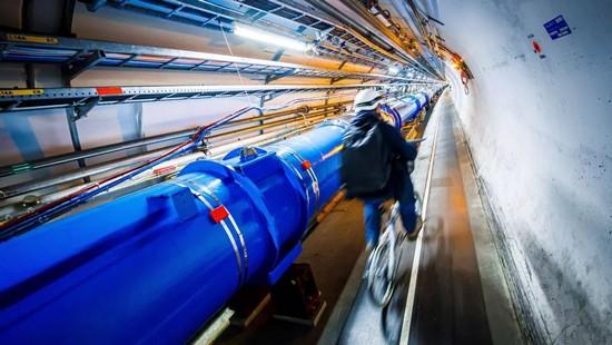 Un uomo va in bicicletta lungo l'acceleratore di particelle al CERN.