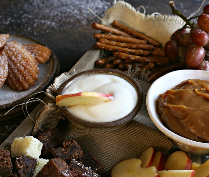 Recipe for creating a dessert treat board with cubes of cake, cookies, fresh fruit, dried fruit and sweet caramel and yogurt dips.