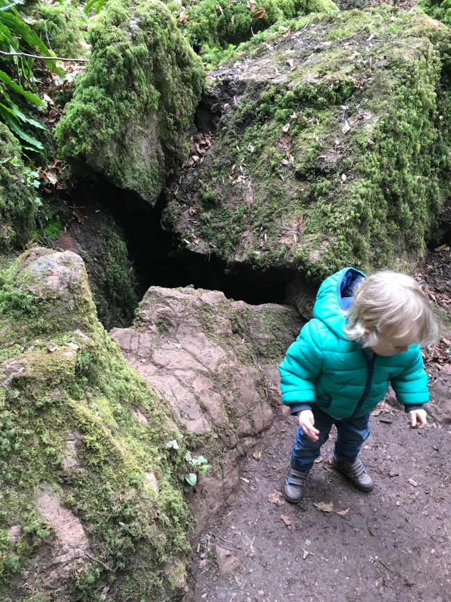 toddler stood by hole in rock