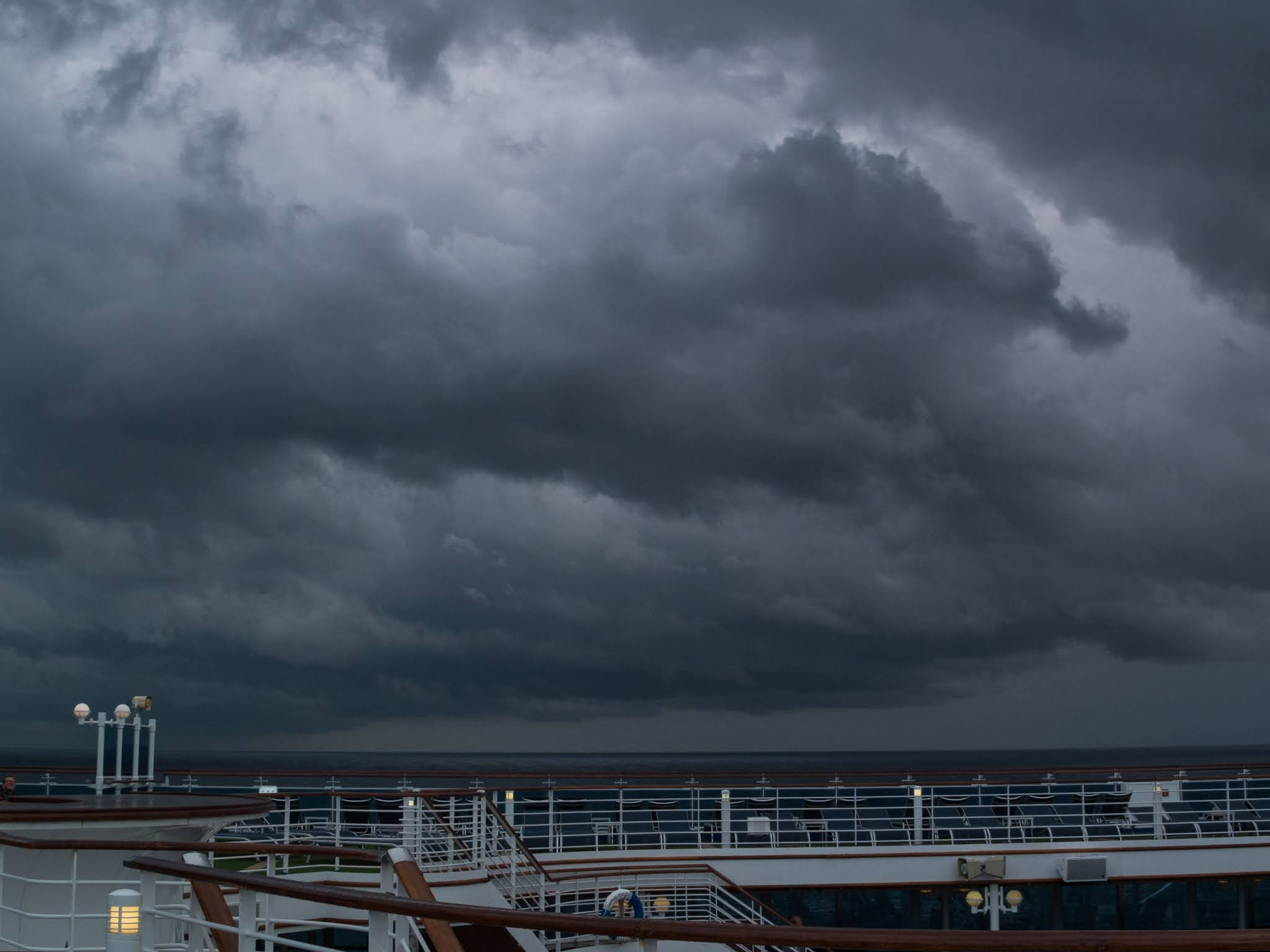 Dramatic clouds looming over an open cruise ship deck.