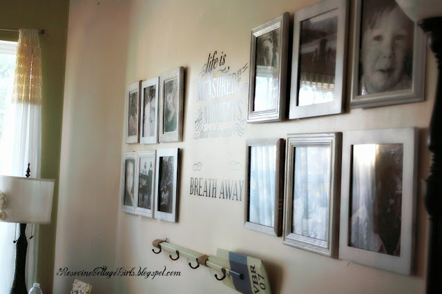 family photos hanging on a wall | sea side living room | rosevinecottagegirls.com