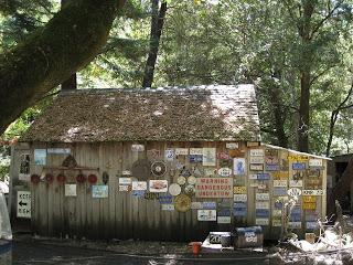 Old wooden building decorated with vehicle license plates and other signs
