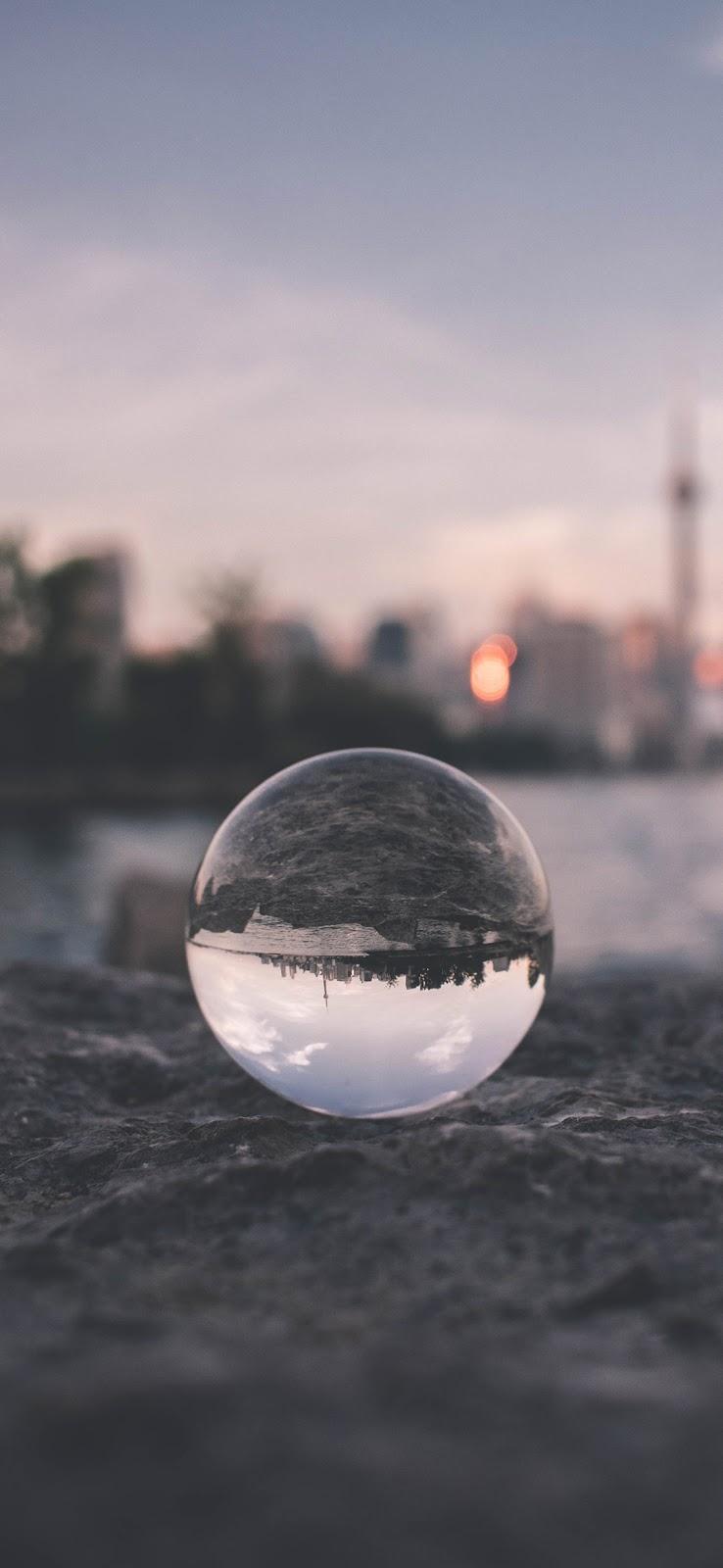 Glass ball on gray sand