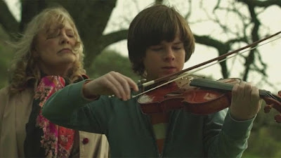 Mercy 2014 movie still where Rebecca (Frances O'Connor) watches and listens to her grandson George (Chandler Riggs) play the violin on a hill outside
