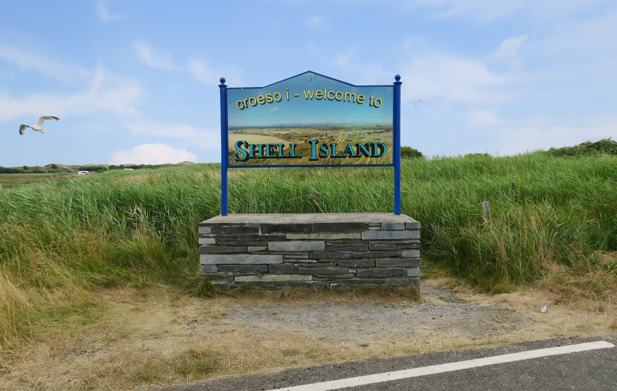 The welcoming entrance sign to Shell Island. Seagulls can be seen flying in the background.